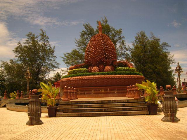 Überdimensionales Durian Fruit Roundabout im Herzen von Kampot. Durian Fruit. Auch bekannt als Stinkfruit. Teuer und gilt in ganz Asien als Delikatesse. Heute ist Kampot vor allem bekannt wegen seines Pfeffers. Aber von den 40ern Jahren bis Pol Pot, soll es in Kampot viele Durian Plantagen gegeben haben, die im Zuge des damaligen Steinzeitkommunismus Reisfeldern weichen mussten.